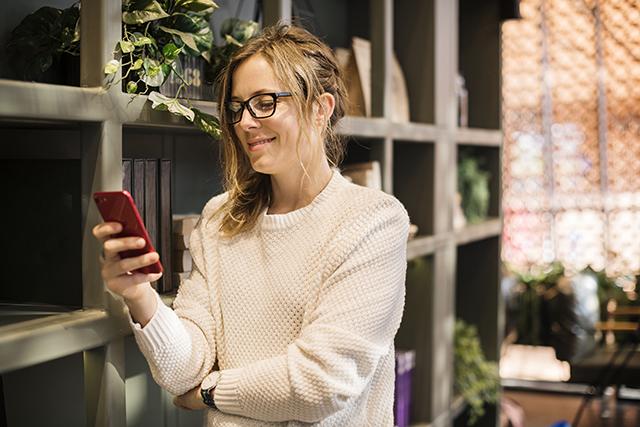 Glad tjej med mobiltelefon
